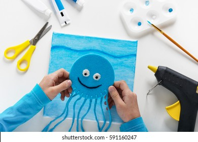 Child used electric hot glue gun to attach blue jellyfish to canvas. Children education concept. Kids crafts. Step 8.