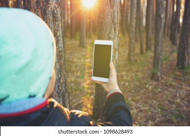 The child uses the phone in nature. Photographing the spring forest with a smartphone. Little traveler spends his leisure time in the woods.