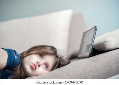 The child uses the tablet for self-education during quarantine. The girl is studying online. A child is looking for information on the Internet.