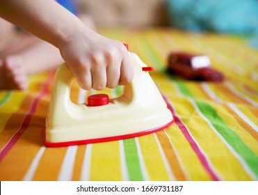 Child uses toy iron in the room