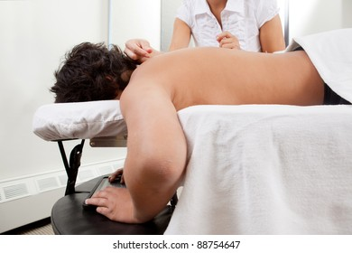 Child using digital tablet with receiving acupuncture treatment in the back