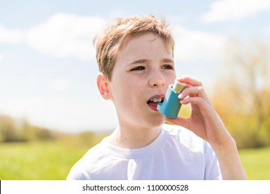 child using inhaler for asthma outside in a park