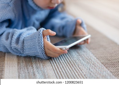 Child is using mobile phone, internet at home. Kid is playing in children games, looking at digital device. Girl in blue knitted sweater is laying on warm floor. Cyber privacy, health security concept