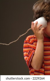A child using a plastic cup telephone
