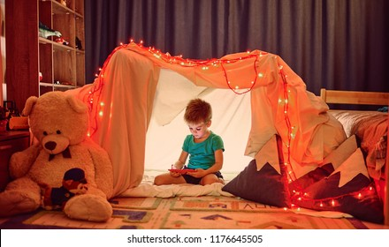 child using tablet pc under blanket at night. Boy with tablet computer in a dark room