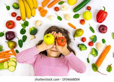 A child with vegetables and fruits in their hands. Selective focus. Food.