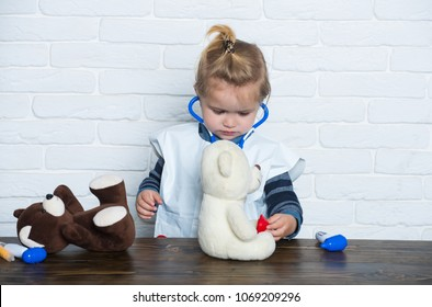 Child veterinarian with stethoscope examine toy animals. Future profession concept. Boy play doctor with teddy bears on white wall. Health, healthcare, medicine. Game, development, imagination.