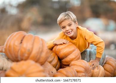 A child in the village has fun near the pumpkin crop.