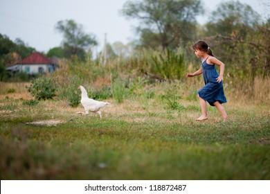 A child in the village runs the hen