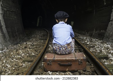 Child in vintage clothes sits on railway road in front of a tunnel.