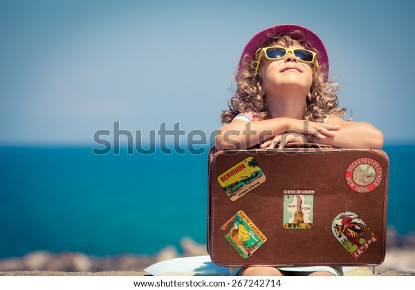 Child with vintage suitcase on summer vacation. Travel and adventure concept