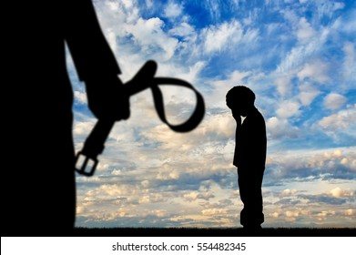 Child violence. Silhouette father with a belt in his hand and a crying boy