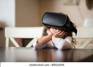 Child with virtual reality headset sitting behind table indoors at home