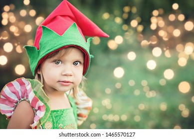 Child waiting for Christmas in wood in juli. portrait of little girl near christmas tree. Baby decorating pine. winter holidays and people concept. Merry Christmas and Happy Holidays. Color bokeh