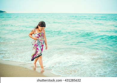 Child walking along the seacoast. Girl in a colorful dress walking on the beach