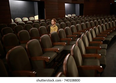 Child walking among rows of chairs in the theater