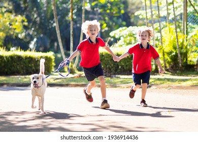 Child walking dog. Kid playing with cute puppy. Little boy running with his pet. Children play in suburban neighborhood street. Animal friends. Friendship and love.