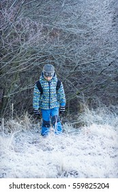 Child walking in frosty nature in cold winter weather.