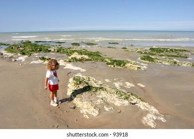 child walking on a low tide beach
