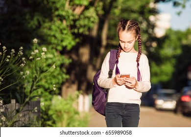 Child is walking with smartphone at sunset