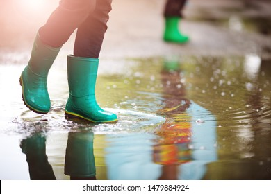 Child walking in wellies and jumping in puddle on rainy weather. Boy under rain in summer outdoors