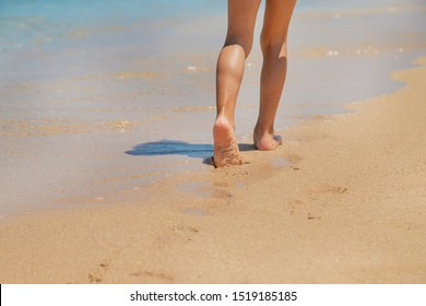 child walks along the beach leaving footprints in the sand. Selective focus. nature.