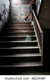 a child walks up an old stairway littered with broken glass