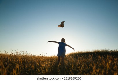 The child walks and plays in nature. Active and energetic little girl throws her straw hat into the air while standing in a wheat field against the sunset sky. Childhood. Summertime. Summer vacation