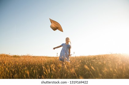 The child walks and plays in nature. Active and energetic little girl throws her straw hat into the air while standing in a wheat field against the sunset sky. Summertime. Childhood. Summer vacation