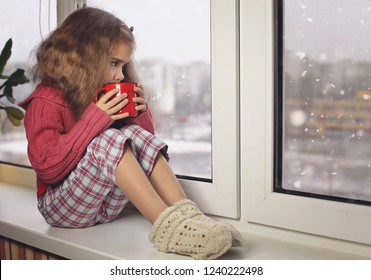 Child in warm comfort sweater drinking a cup of hot chocolate, relaxing on a window sill and looking on the snow. Lazy weekend, cozy scene, hygge concept.