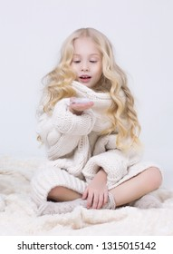 A child in a warm knitted sweater holds a feather in his hand.