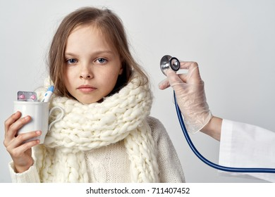 child in a warm woolen scarf holding a mug with pills ill with flu, a doctor's hand with a stethoscope