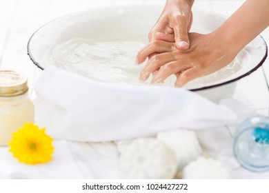 Child washes his hands in the white bowl , nearby are handmade soaps, flower and cream, cleanliness and hygiene concept