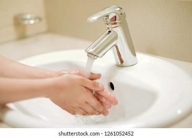 Child washing hand with soap. Boy washing hand . kid washing hands in bathroom