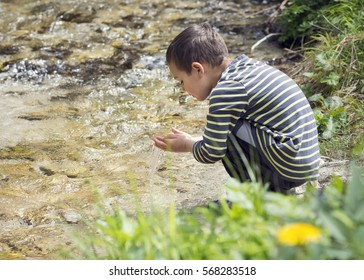 Child  washing hands or drinking water from clean mountain river, environmental concept.