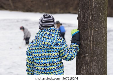 Child watching other children playing ice hockey on a frozen lake or river