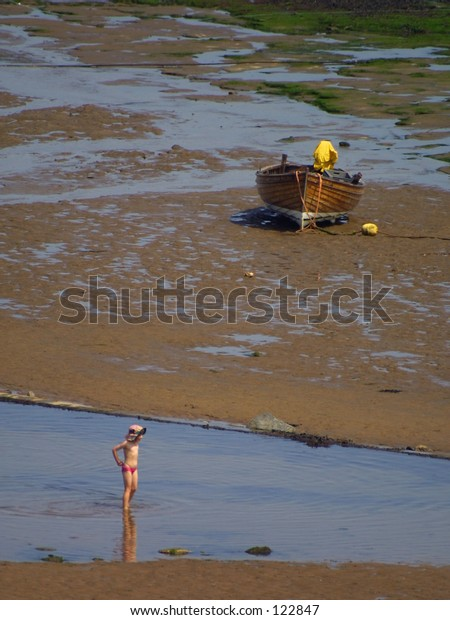 Child in water with boat in background. Robin Hood Bay, North Yorkshire, UK.