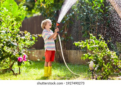 Child watering flowers and plants in garden. Kid with water hose in sunny blooming backyard. Little boy gardening. Summer fun outdoor at home. Family activity in spring. Children help parents.