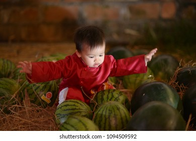 A child wear ao-dai traditional costume viet nam and sell watermelon.