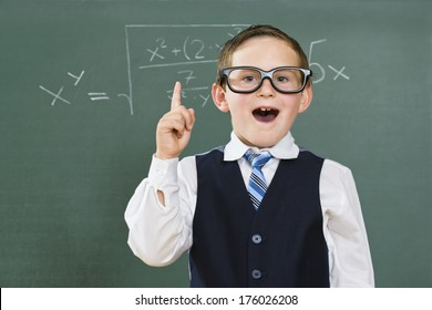 A child wearing big spectacles and solving math sums.