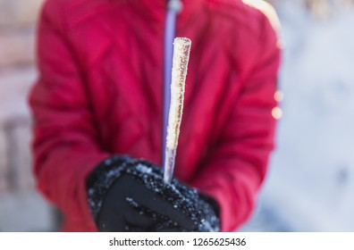Child wearing black gloves and a red jacket holds an icecicle in winter time.
