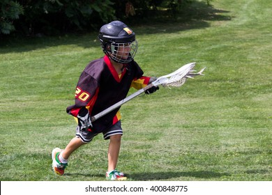 Child wearing black jersey and protective equipment playing lacrosse in the park