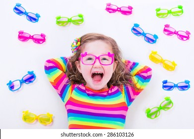 Child wearing eye glasses. Eye wear for kids. Little girl choosing spectacles. Lens and colorful frame choice for children. Vision and sight control at optician shop. Smart preschooler with eyeglasses