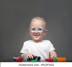 child wearing glasses sitting at the table and playing with toys