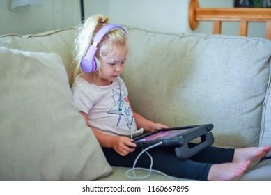 child wearing headphones looking at tablet computer watching movie