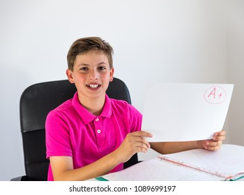 child wearing a pink shirt showing proudly his score obtained in a school exam