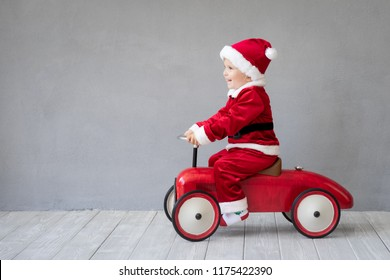 Child wearing Santa Claus costume. Kid playing at home. Baby having fun at Christmas time. Merry Xmas concept