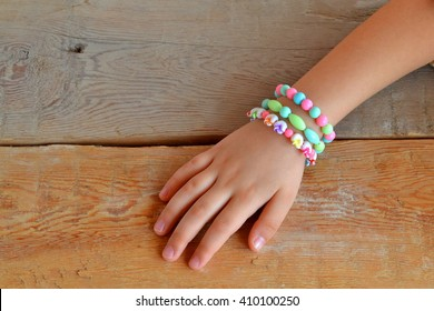 Child wears bracelets on his hands. Child hand wearing bracelets. Bracelets from plastic beads. Old wooden background
