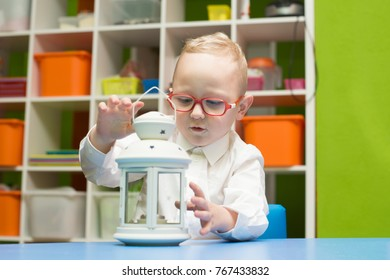 A child wears glasses and a white shirt, sits at a table in the children's playroom