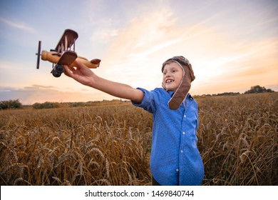 child in a wheat field in a hat and Aviator glasses in the village with a retro plane in his hands. boy dreams of becoming a pilot. evening beautiful sky over meadow of grain. dreams of flying planes
